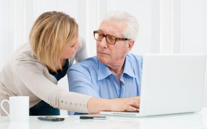 female helping mature male to use a computer