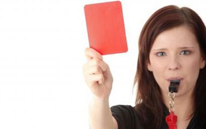 Female referrer blowing whistle holding red card