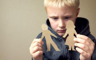 upset boy with paper people cut outs